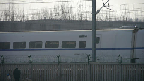White high-speed train between the wire,People in railway side Footage