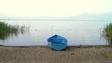 Small fishing boat on lake coastline Footage