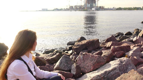 Woman sit at shore stones, then look across water to tower construction site Footage