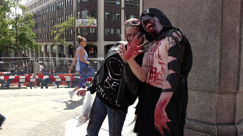 The Facelift Monster posing in a public square with a zombie woman Footage