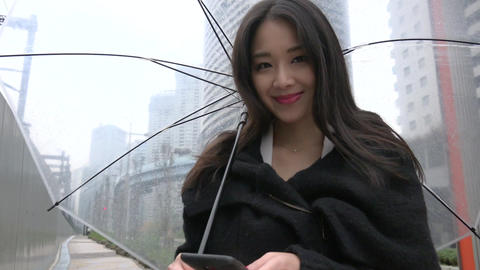 Technology With Asian Woman Texting Using Smartphone In The Rain