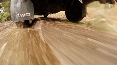 Truck drives down dirt road and through water hole Footage