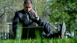 Businessman works with laptop and mobile phone in the city park Footage