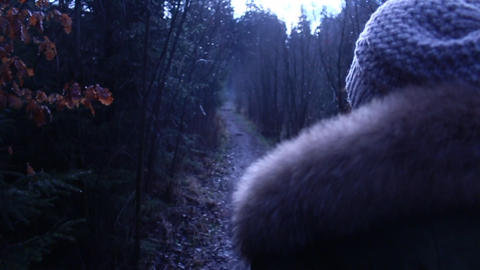 Woman Walking through the forest in autumn with fur jacket and beanie over the s Footage