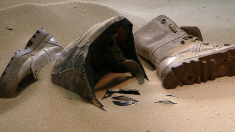 soldier hat boots and sand glass in the desert Filmmaterial