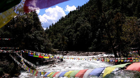 Bhutan river with prayer flags from a bridge Footage