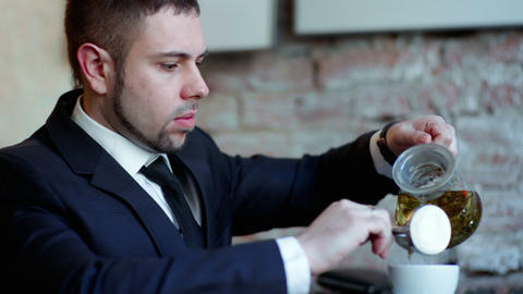Businessman drinks tea at the cafe Footage