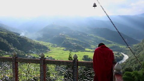 Bhutan monk on top of a monastery with view over Punakha area Footage