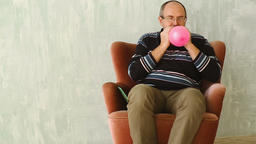 Senior man sitting and inflating the balloon Footage