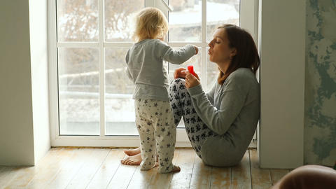 Mother and daughter blowing bubbles indoor Footage