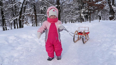 Small child dressed in pink overalls who goes after him a sled on a snowy alley  Footage