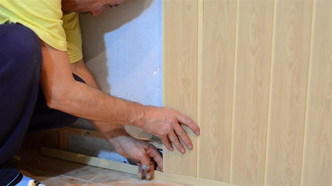 Worker assembles wood-paneled walls of the kitchen 1 Footage