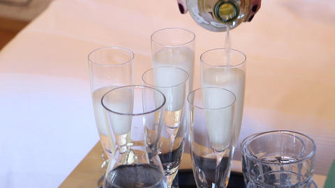 Sparkling wine filling in glasses at a wedding pouring Live Action