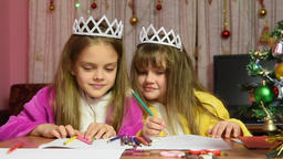 Sisters swearing and jostling drawing at a table in a Christmas setting Footage