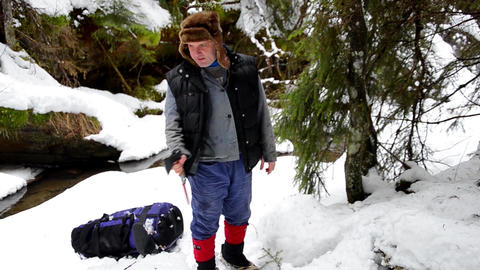 Forestry worker who takes an ax from snow look at something lying on the ground  Footage