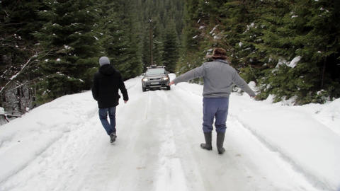 Men and machine that descends on a slippery road from snowy fir forest 14 Footage