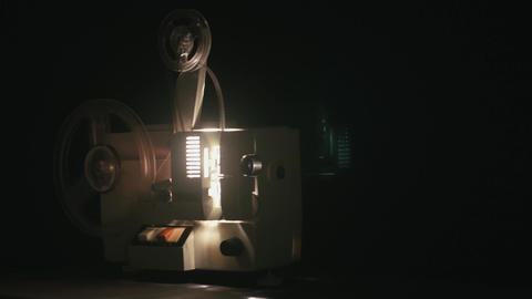 Old film camera projection is started by hand by a man then stops it after a whi Live Action