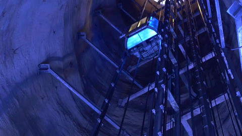Lift of people moving through a deep well lit with blue light 93p2 Footage