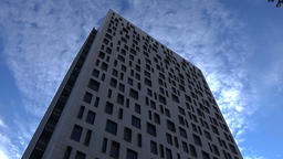 Low angle view on tall modern glass building on blue sky with white clouds abstr Footage
