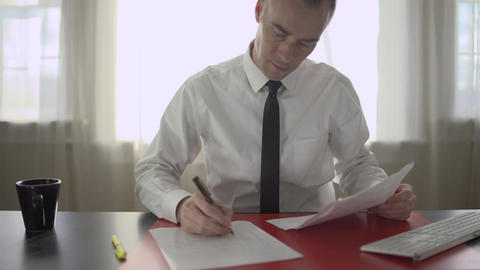 Successful man doing paperwork at his desk Footage