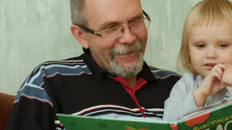 Close-up of grandfather read a book to her little granddaughter Footage