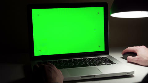 Man use a laptop on his desktop with a green screen Footage