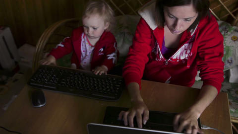 Mother and daughter works on laptop Footage