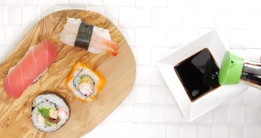 Pouring soy sauce in dish beside sushi Footage