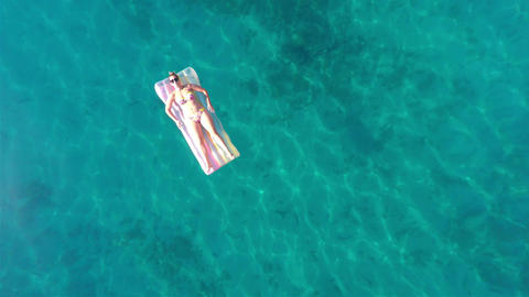 Woman on the beach mattress aerial view Footage