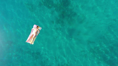 View at woman lying on beach mattress aerial view Footage