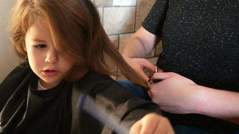 Young girl getting a haircut at a hair salon Footage