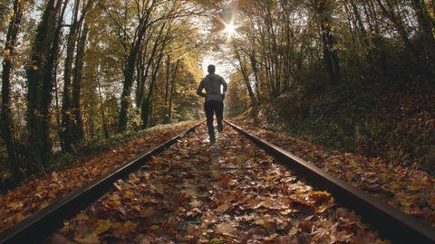 Fisheye POV Angle of Man Jogging Down Train Tracks in Fall Season Footage