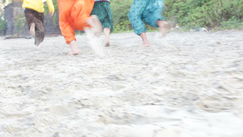 guys in Indian national clothes run along sand beach one falls Footage