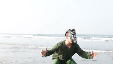guy in ritual mask jumps frightens somebody in shallow sea Footage