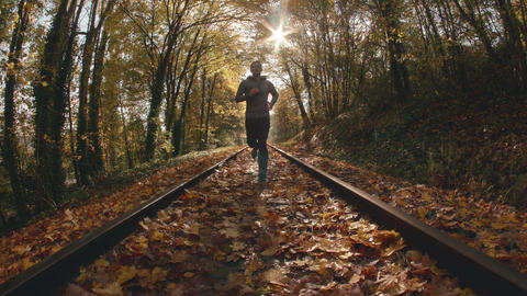 Fisheye POV Angle of Man Jogging Up Train Tracks in Fall Season Footage