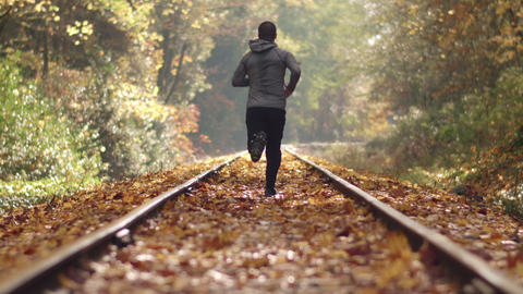 Man Jogging Down Train Tracks in Autumn Season with Leaves Falling and Deep Focu Footage