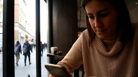 Worried woman typing on mobile phone in cafe Footage