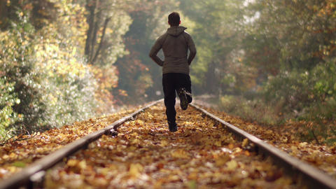 Man Jogging Down Train Tracks in Autumn Season with Leaves Falling and Medium Fo Footage