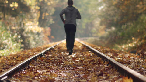 Man Jogging Down Train Tracks in Autumn Season with Leaves Falling and Shallow F Footage