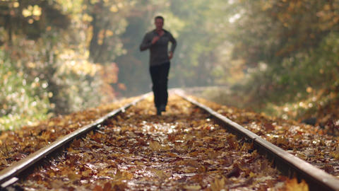Man Jogging Up Train Tracks in Autumn Season with Leaves Falling and Shallow Foc Footage