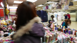 Woman choosing fabric roll from heap of, textile market, moving camera Footage