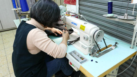 Woman push fabric to sewing-machine and stitch it, dressmaker work Footage