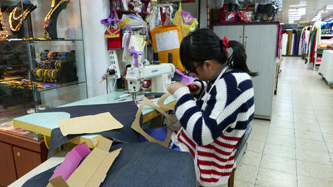 Girl in glasses cuts out a template pattern of cardboard, Yongle Fabric Market Footage