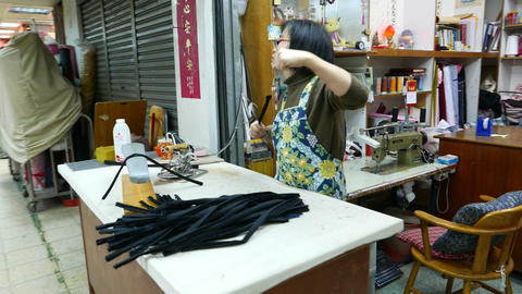 Female tailor make preparations from strips of fabric, camera fly around Live Action