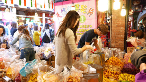 Pretty taiwanese girl sell dried fruits on market, offering to taste POV Footage