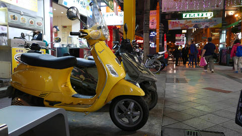 Yellow Vespa motorbike parked on night street. People walk on background Footage