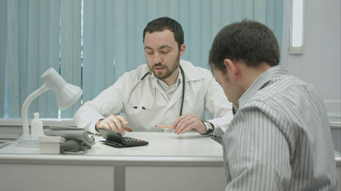Male bearded doctor in clinic calculate high price for treatment Footage