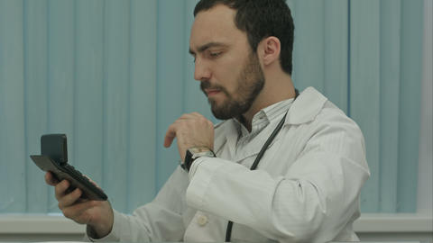 Serious male doctor focus on calculation of costs and revenues Live-Action