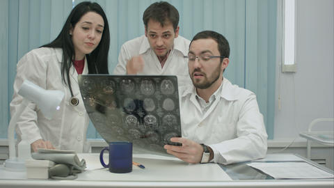 trio of young afraid physicians checking patient's head scanning Live Action