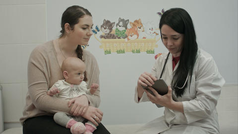 female pediatrician doctor shows something on tablet to woman with small baby Live影片
